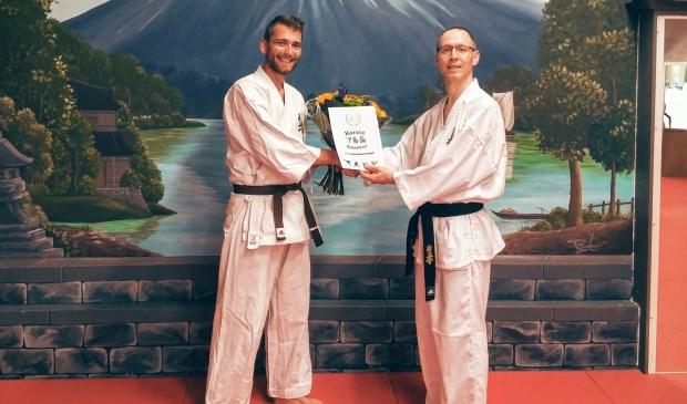 Sensei Alwin Ikink (r) feliciteert Erik Wolterink (l) met zijn jubileum.