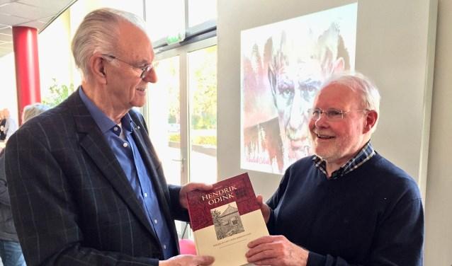 Ben Tragter (r) reikt het eerste exemplaar met niet eerder uitgebracht werk van Hendrik Odink uit aan achterneef Gerrit Odink (l) in Kulturhus 't Spieker in Eibergen. Foto: Susanne ten Have