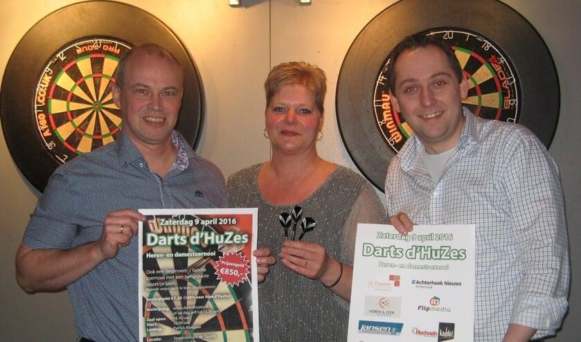 Arjan Kocken (links), De Tuunte-horecamedewerkster Patrice van Zuidam en Niels Blikman tonen posters die worden gebruikt om Darts d´Huzes te promoten. Foto: Bart Kraan