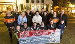 Vrijwilligers van het Sjoksfestival bijeen met het spandoek dat het jubileumfestival aankondigt. Foto: Jurgen Pillen