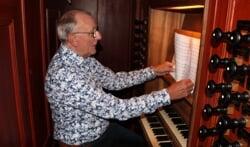 Gerrit Hietkamp zoekt, gezeten achter het orgel van Jacobskerk, een mooi psalm uit om te spelen. Foto: Lydia ter Welle