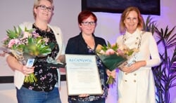 Burgemeester Vermeulen reikt Meander uit aan Jenneke Golstein (l) en Helga Blei van de stichting Wie Goed Doet Goed Ontmoet (WGDGO). Foto: Alize Hillebrink