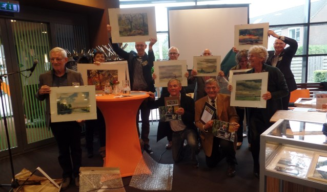De kinderen van Thate schenken een schilderij aan de vrijwilligers. Foto: Meike Wesselink