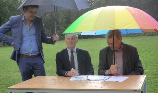 Peter van de Wardt (r) en Henk van der Esch tijdens de ondertekening in de regen. Foto: Walter Hobelman
