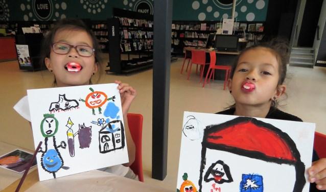 Dina (l) en Monika, met een van de bieb gekregen magic snoepgebitje, showen hun kunstwerken. Foto: Josée Gruwel