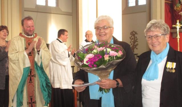 Franci Kock en Lies Hebing (r) kort na de onderscheiding door de applaudisserende pastoor Jurgen Jansen. Foto: Dinie Gasseling