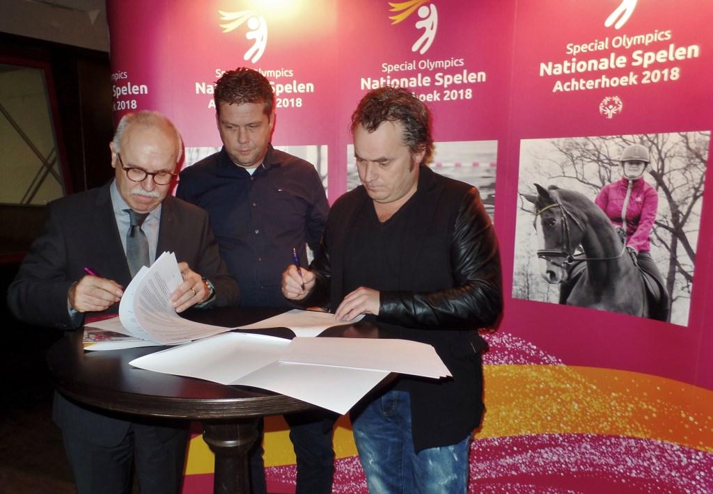 Ronnie Degen en René van Gils tekenen onder Feestfabriekmedewerker Erik Dreteler de samenwerkingsovereenkomst. Foto: Henri Walterbos  © Achterhoek Nieuws b.v.