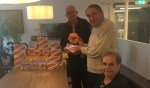 Henk Reitsema (tweede staand van rechts) schenkt bewoners Pardijs een doosje chocolade en een pak koekjes. Foto: PR.