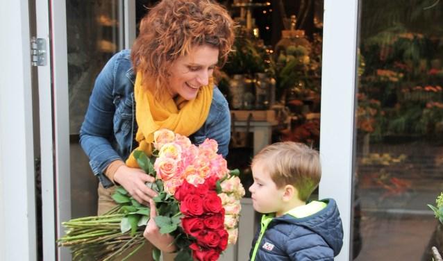 Janet Buiting van Altijd Bloemen laat haar jonge klant Ruben ruiken hoe heerlijk de rozen geuren. Foto: Lydia ter Welle