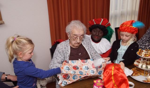 De kleinkinderen hielpen maar wat graag bij het uitpakken van de cadeautjes. Foto: Frank Vinkenvleugel