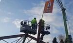 """De vlag in top door medewerkers van de bouwplaats. """"Zelf waog ik dat neet,"""" aldus Jos Oostendorp nippend aan het pannenbiertje. Foto: Henri Walterbos"""