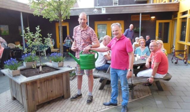 Bestuursvoorzitter Theo Verhoeven (rechts) geeft een gieter aan bewoner Henk Geessink (links) waarmee de symbolische overhandiging een feit is.Foto: PR