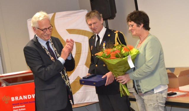 Koninklijke onderscheiding voor Tonny Graven, bloemen voor zijn vrouw Rita. Links burgemeester Arnold Gerritsen. Foto: Karin Stronks