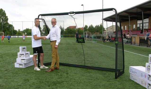 Marcel Dijk, rechts, overhandigt VIOD jeugdtrainer Jos Mekkes 8 pupillendoeltjes. Foto: PR