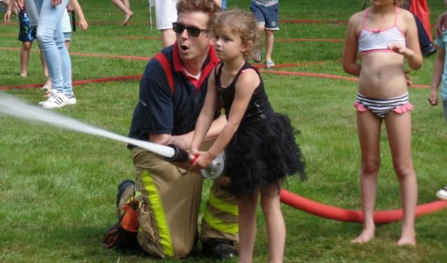 Het was best wel spannend om de de krachtige brandweerslang te mogen vasthouden. Doto: Jan Hendriksen.