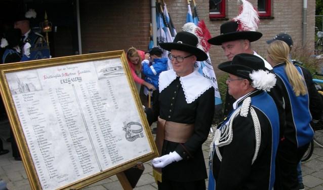 Wim Land en Simon Dekker overhandigen de plaquette aan voorzitter Gerard Huntink (vlnr). Foto: John van der Kamp