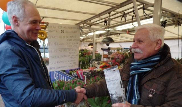 Uit handen van Rein de Heus ontving Ton van den Breemen (l) een 'fles met inhoud'. Foto: Jan Hendriksen