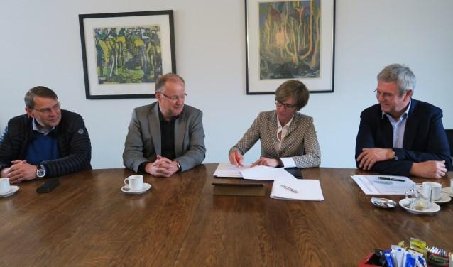 Gadegeslagen door Jos Rouwmaat links en Vincent van Uem rechts, zetten Annette Bronsvoort en Hans Rouwmaat hun handtekening onder de intentieverklaring. Foto: Theo Huijskes