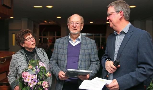 Gerard Schepers (m.) en zijn vrouw Annie werden tijdens de nieuwjaarsbijeenkomst in het zonnetje gezet door voorzitter Henk Sleumer. Foto: PR