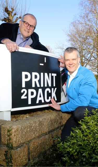 Rob van Dijk (links) en Gerhard Weevers bij het nieuwe logo van Print2Pack. Foto: Dominique Weevers