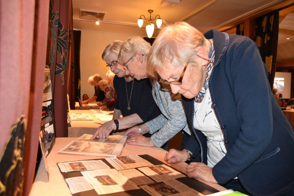 Oude krantenberichten en foto's kijken over uitjes en lezingen van weleer. Foto: Alice Rouwhorst  © Achterhoek Nieuws b.v.