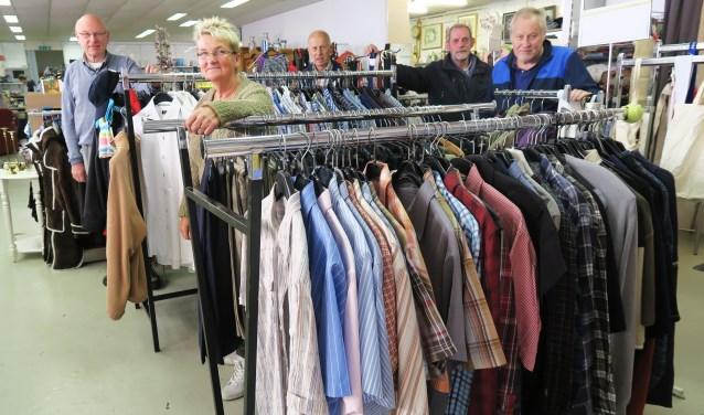 Enkele vrijwilligers met geheel links Jan ter Dolle in de Vincentius-winkel. Foto: Theo Huijskes