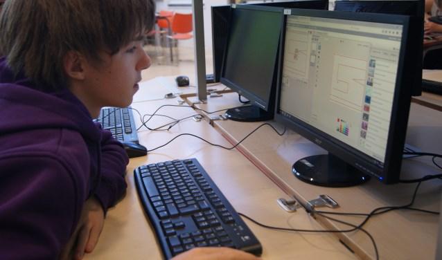 Ingespannen aan de slag met programmeren. Foto: Martijn Bos