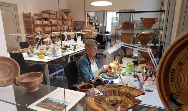 Vrijwilligers Archeologie geven uitleg over het restaureren van aardewerk objecten. Foto: PR