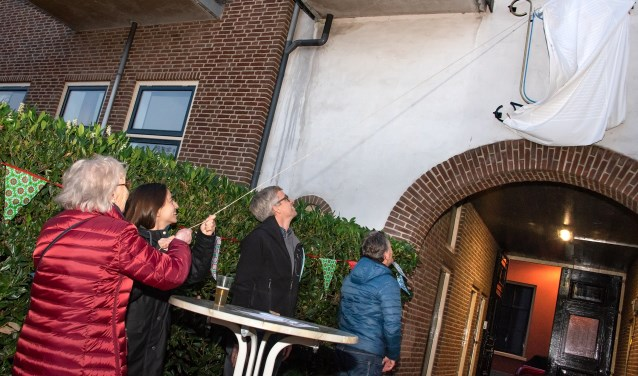 Harmke Schalkwijk en Marie-Nour Hartman onthullen het logo aan het Wöhrmannhofje. Foto: Willem Feith