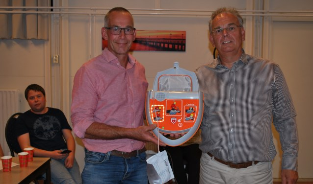 Jan Willem Jolink, voorzitter van buurtvereniging Wassinkbrink, neemt de AED in ontvangst van de firma Cardi Aid. Foto: Margreet Nusselder