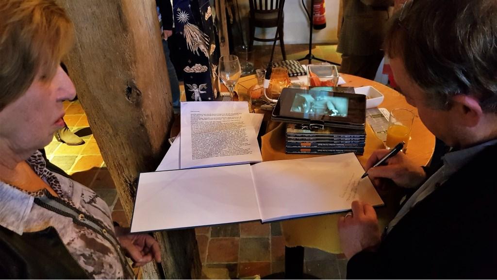 Zoals het een schrijver betaamt signeert Frans Helmich op verzoek zijn boek. Foto: Alice Rouwhorst  © Achterhoek Nieuws b.v.