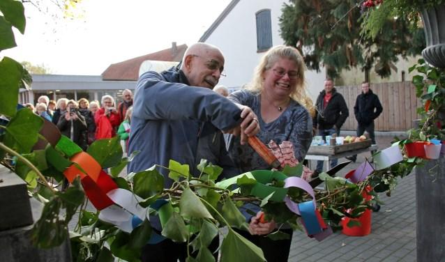 Meester Arnold Janssen helpt Josja van Mierlo met de officiële opening van haar bloemenlokaal. Foto: Liesbeth Spaansen
