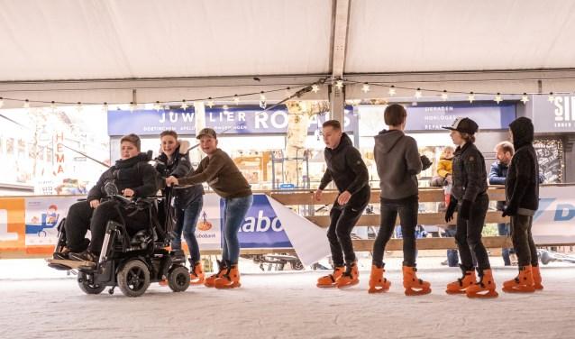 Jayden kreeg toestemming om met zijn rolstoel en zijn vrienden de ijsbaan op te gaan. Foto: Burry van den Brink