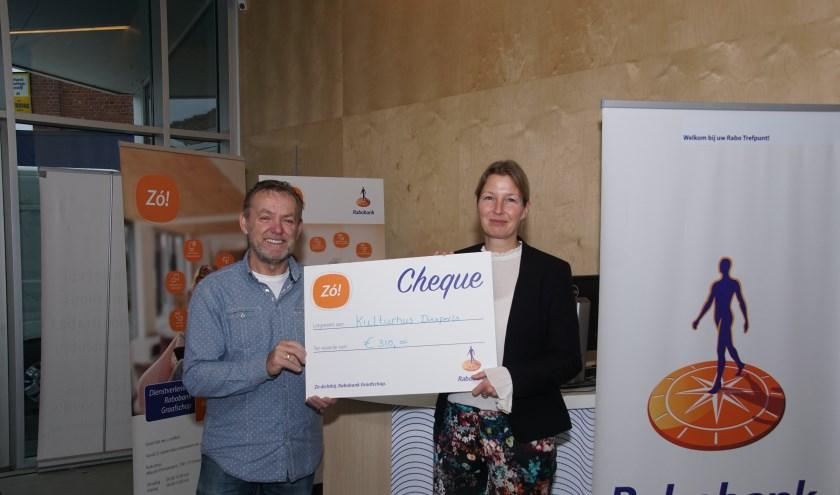 Theo Janssen en Tamara Elburg tonen de symbolische cheque die zij ontvingen van de Rabobank. Foto: Frank Vinkenvleugel