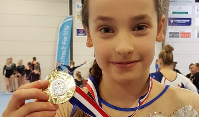 Lina toont trots haar gouden medaille.