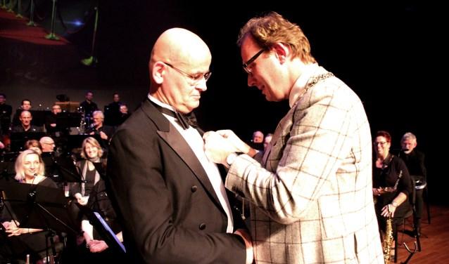Dirigent Joop Boerstoel krijgt de zilveren eremedaille van de gemeente Doetinchem uitgereikt door burgemeester Mark Boumans. Foto: Han Gerritsen