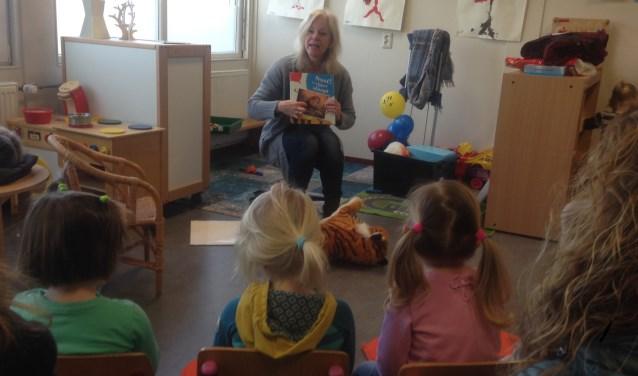 Peuters luisteren naar voorlezer Jenny van de bibliotheek. Foto: Saskia te West