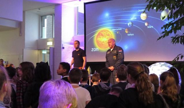 André Kuipers en Sander Koenen (links) gooiden zojuist een balletje de zaal in om uit te leggen hoe een raket het handigst in een baan om de aarde kan worden gebracht. Foto: Josée Gruwel