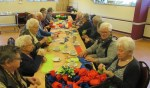 Gasten van de Keijkamer maken roosjes voor de KBO. Foto: PR