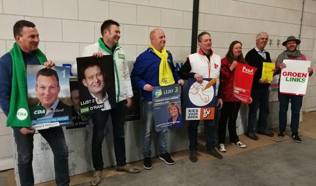 De lijsttrekkers staan klaar om hun affiches aan te plakken. Foto: Rob Weeber