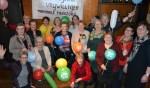 Agnes Berendsen (oranje ballon en bloemencorsage) te midden van het team vrijwilligers van Hospicegroep de Lelie. Geheel rechts: Joke Verwey.Foto: Leander Grooten