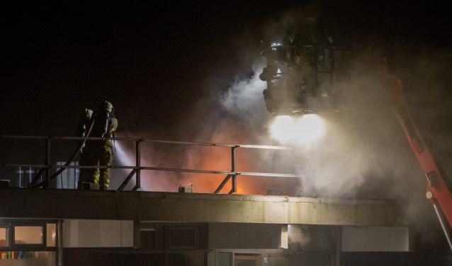 Brandweerlieden blussen op het dak van de flat aan de Caenstraat. Foto: News United/112 Achterhoek Nieuws
