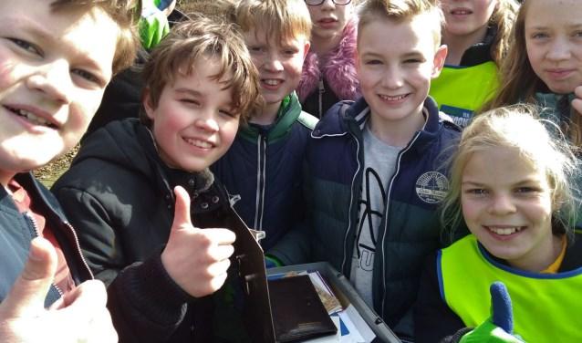 Mika met het geldkistje tussen klasgenoten. Foto: Henri Walterbos