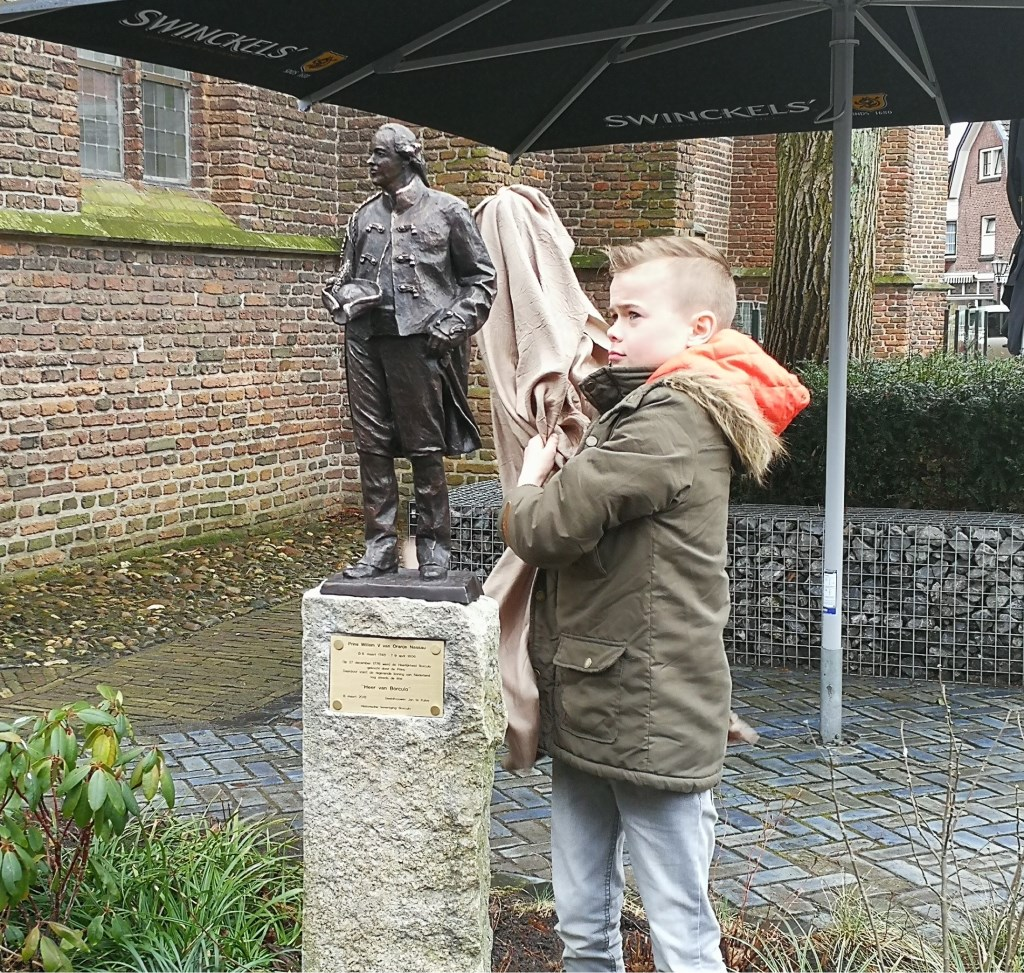 De vijfde generatie 'Willem' Nieuwenhuis, zoon Marc Cornelis Willem, onthult het beeld van Willem V. Foto: Rob Weeber