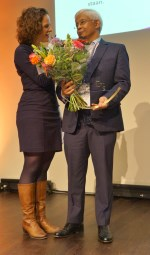 Richard Geeraths van PMS heeft zojuist de eerste Unieke Werkgever Award en een bos bloemen ontvangen. Hij wordt geïnterviewd door dagvoorzitter Maud Wilms (links). Foto: Richard Stegers