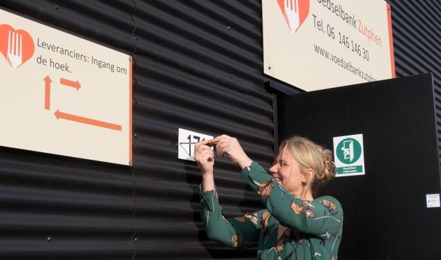 Annelies de Jonge schroeft het nieuwe huisnummer op het pand van de voedselbank. Foto: PR