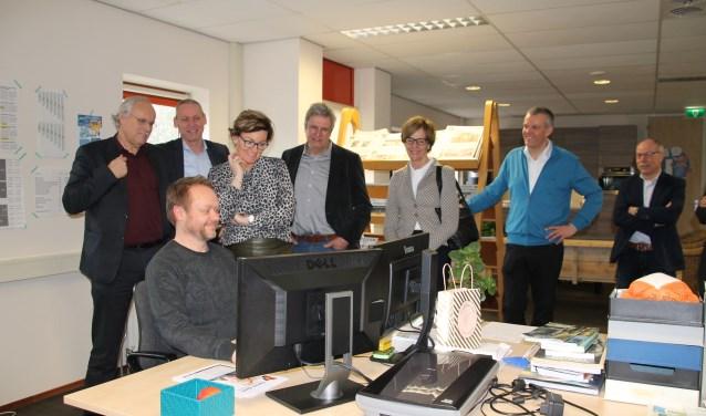 Het college kijkt toe, hoe vormgever Nick Oostendorp bezig is met de gemeentepagina's van Oost Gelre, die wekelijks in de Elna en de Groenlose Gids worden gepubliceerd. Foto: Lydia ter Welle