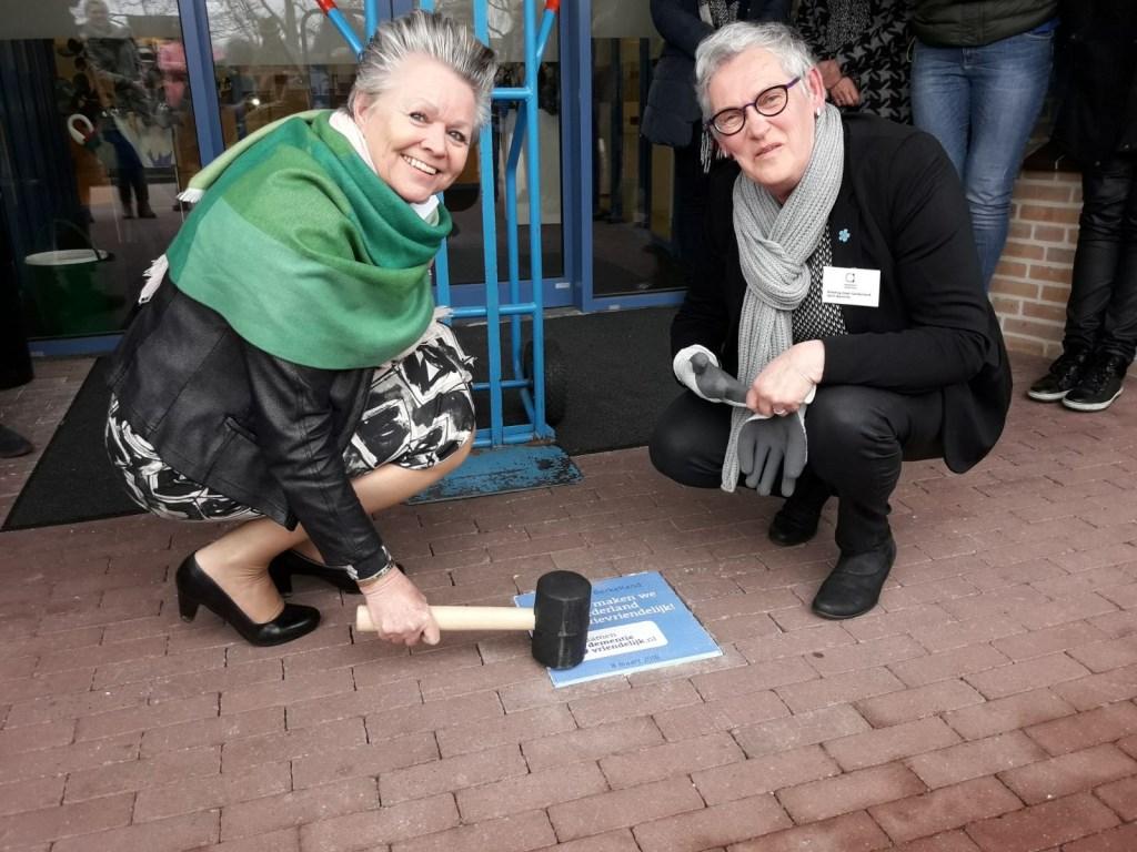 Wethouder Marijke van Haaren en Gerri Bannink leggen de tegel. Foto: Gemeente Berkelland