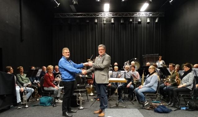 Wim Lammers overhandigt 'het stokje' aan de nieuwe dirigent Henk Jan Radstaak (r). Foto: Camiel Steverink/PR Excelsior
