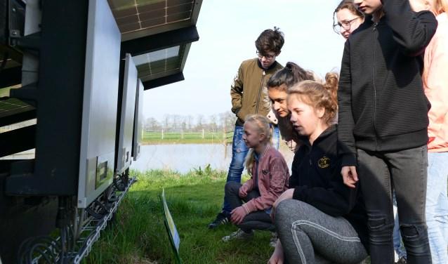 Kinderen bestuderen een display op een omvormer, waarop is te lezen hoeveel zon is geoogst en hoeveel energie dat oplevert. Foto: PR